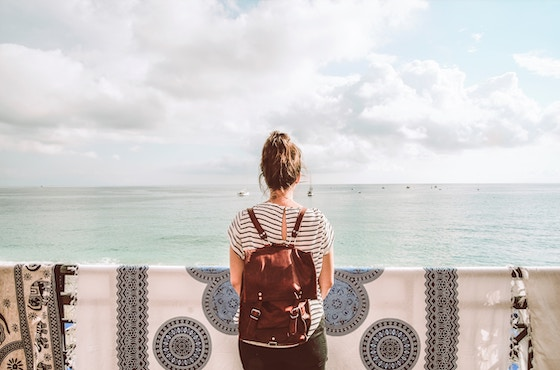 Girl with a backpack in front of the ocean