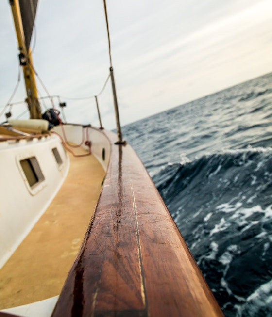 Side of a sailing boat crusing through the ocean