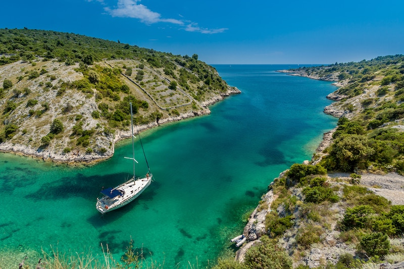 Sailboat sailing between two pieces of land in Trogir, Croatia