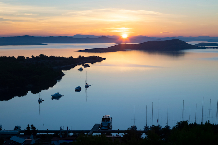 Sunrise over the croatian coast with boats anchored
