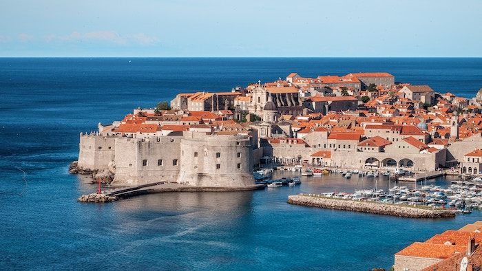 Aerial view of the old city of dubrovnik and the marina with sailboats.