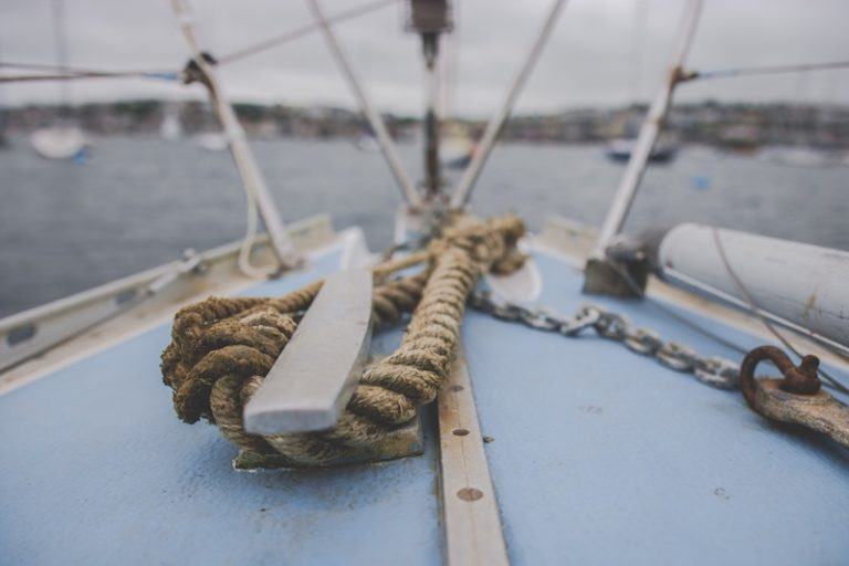 Sailing boat in the water knoted with an old rope.