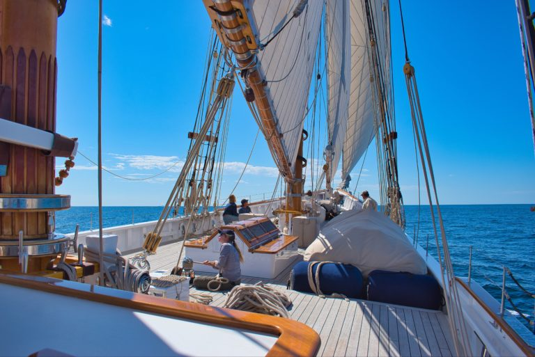 People on a sailing boat with the sails up and a girl fixing the ropes.