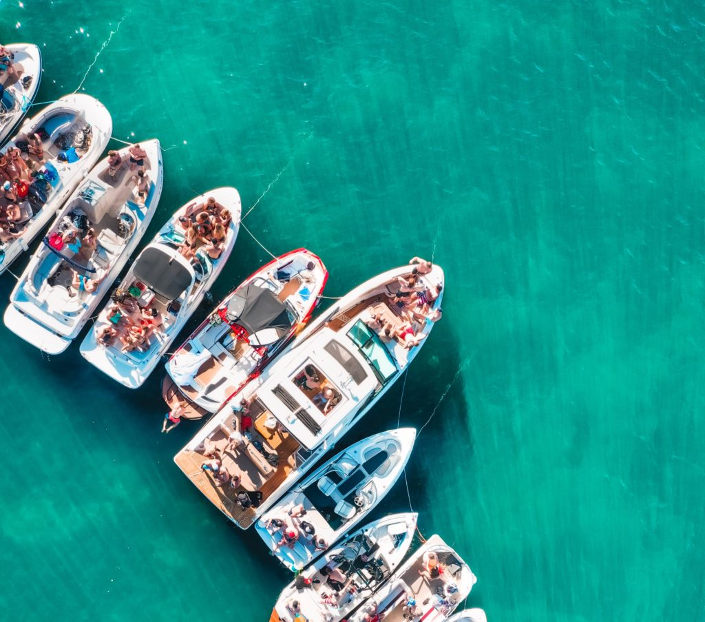 Aerial view of people partying on the boat around the coast.
