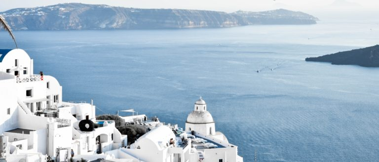 White concrete buildings near ocean during daytime in Greece.