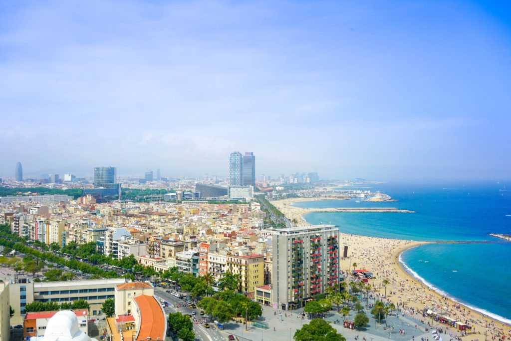 Aerial view by day of Barcelona city, with the view on the sea and people laying on the beach.