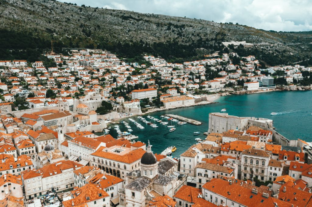 Aerial view of the port of Dubrovnik with boats, old buildings and camel roofs.