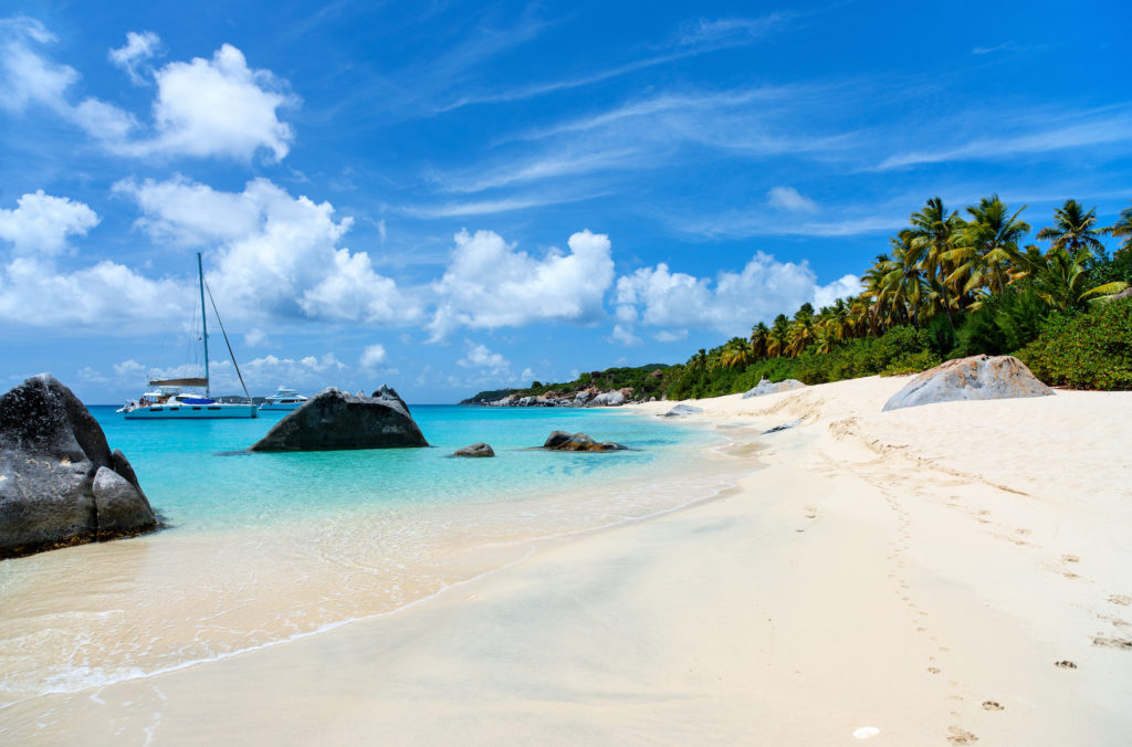 one of the sandy beaches on Virgin Gorda in BVI with a catamaran