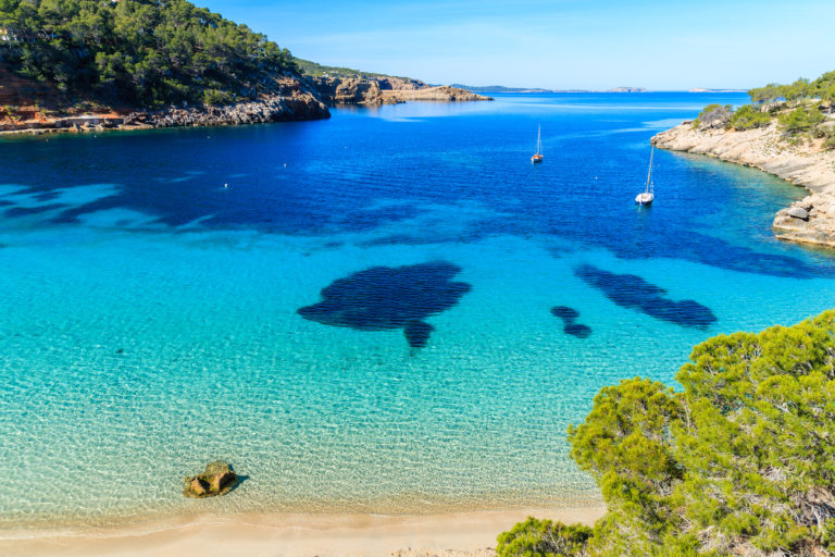 Aerial view of a bay in Ibiza, Spain including clear blue sea, two boats and the surrounding coast with trees