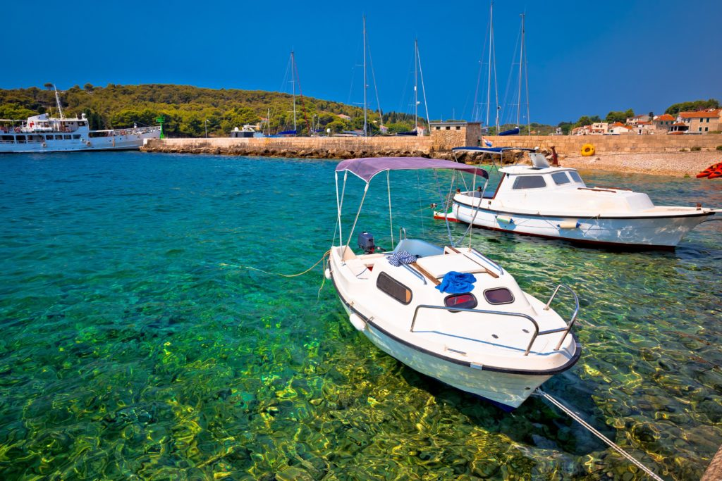 Two boats in the bay of Prvic in Croatia with clear water and blue sky