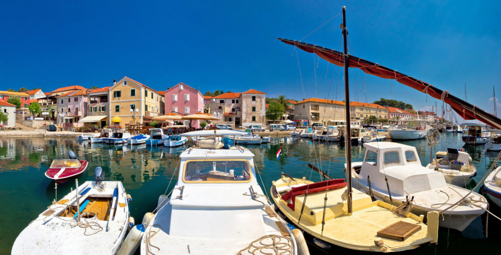 Overview of the port of Sali in Croatia with multiple boats, colourful buildings and clear blue sky