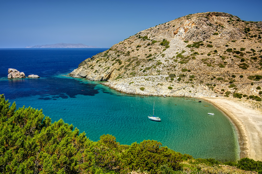 A sailboat sailing in a secret cove in Kithnos, Greece