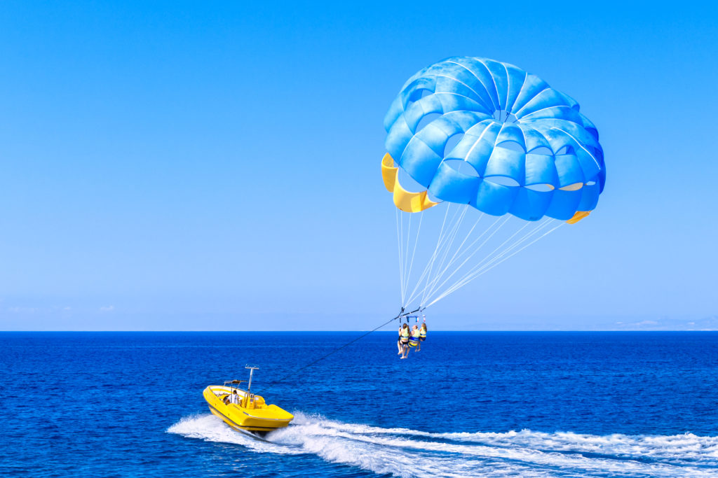 3 people parasailing on the sea pulling by the yellow motor boat