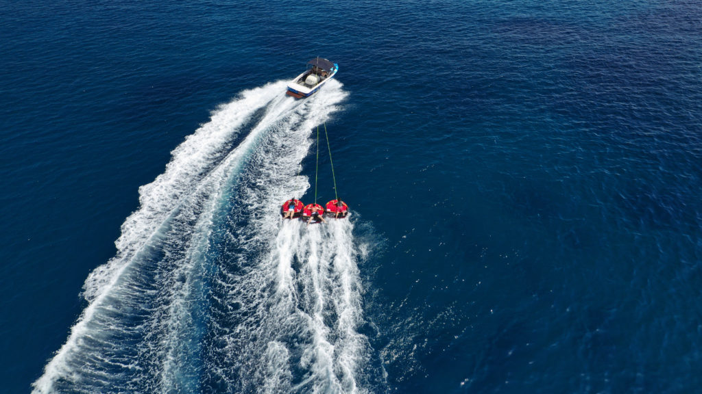 A motor boat pulling 3 inflatables on the sea