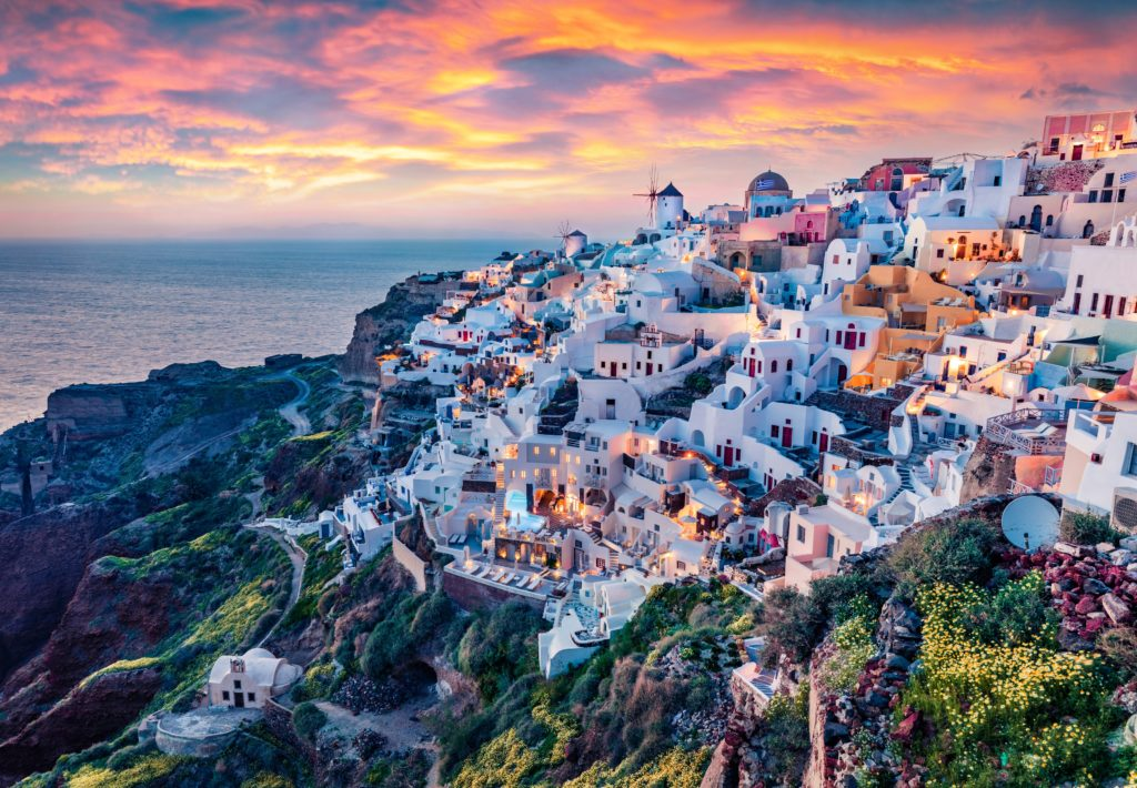 View of the sunset in Oia, Santorini with the beautiful landscape of the buildings and the sharp cliff