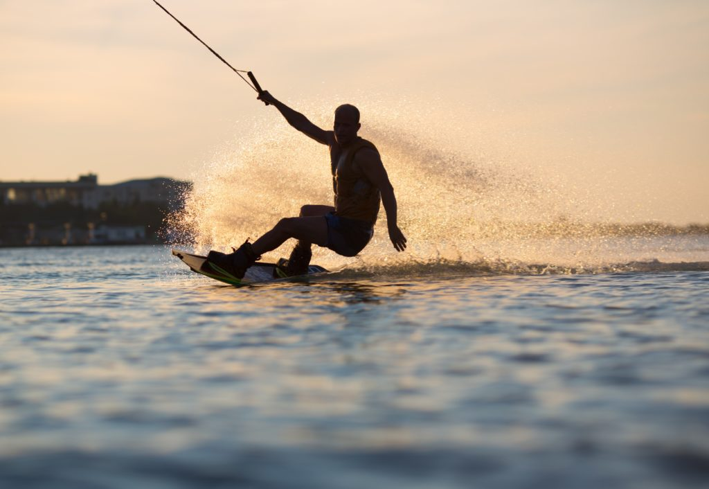 A boy wakeboarding on the sea in the sunset