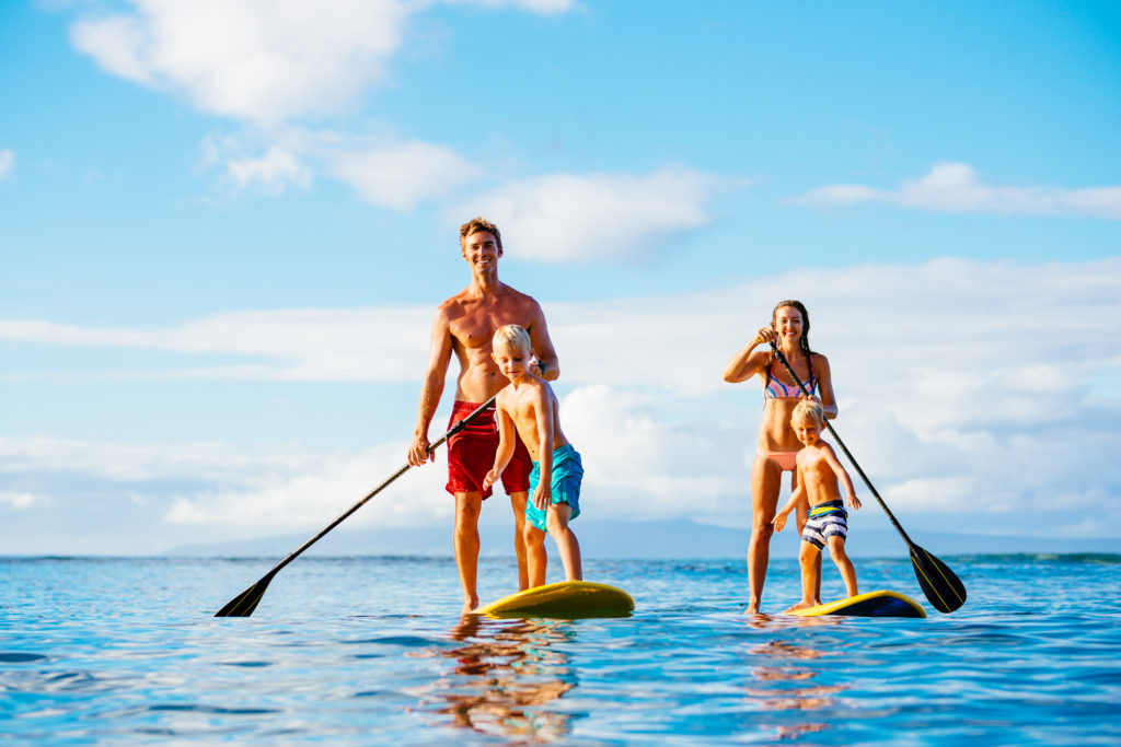 A family of 4 happily standing up on the paddleboard on the sea