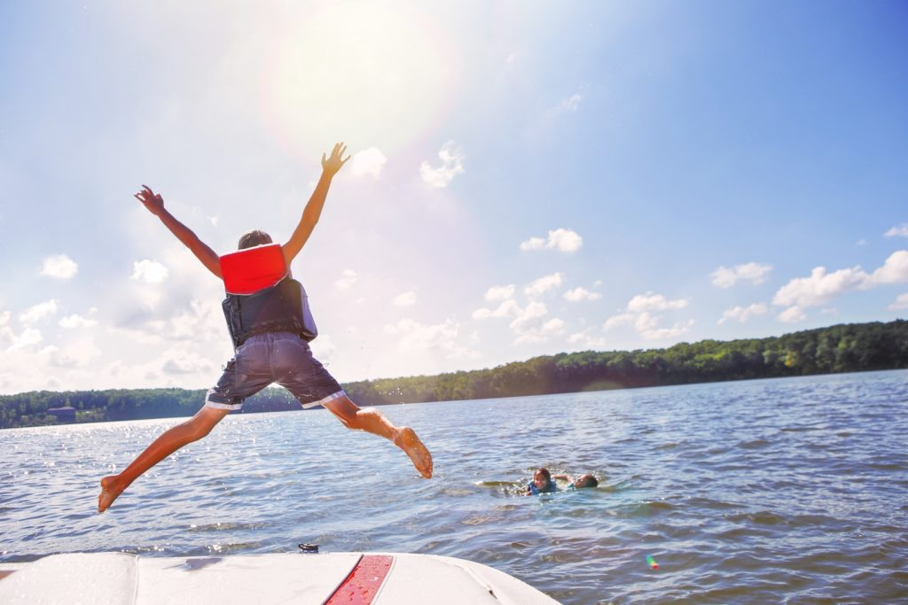 View of a kid jumping in the water from a boat.