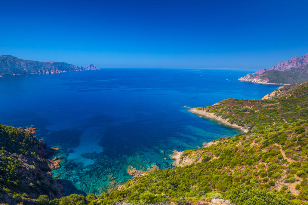 An aerial view of a bay in Girolata displaying rocks, greenery and deep blue sea
