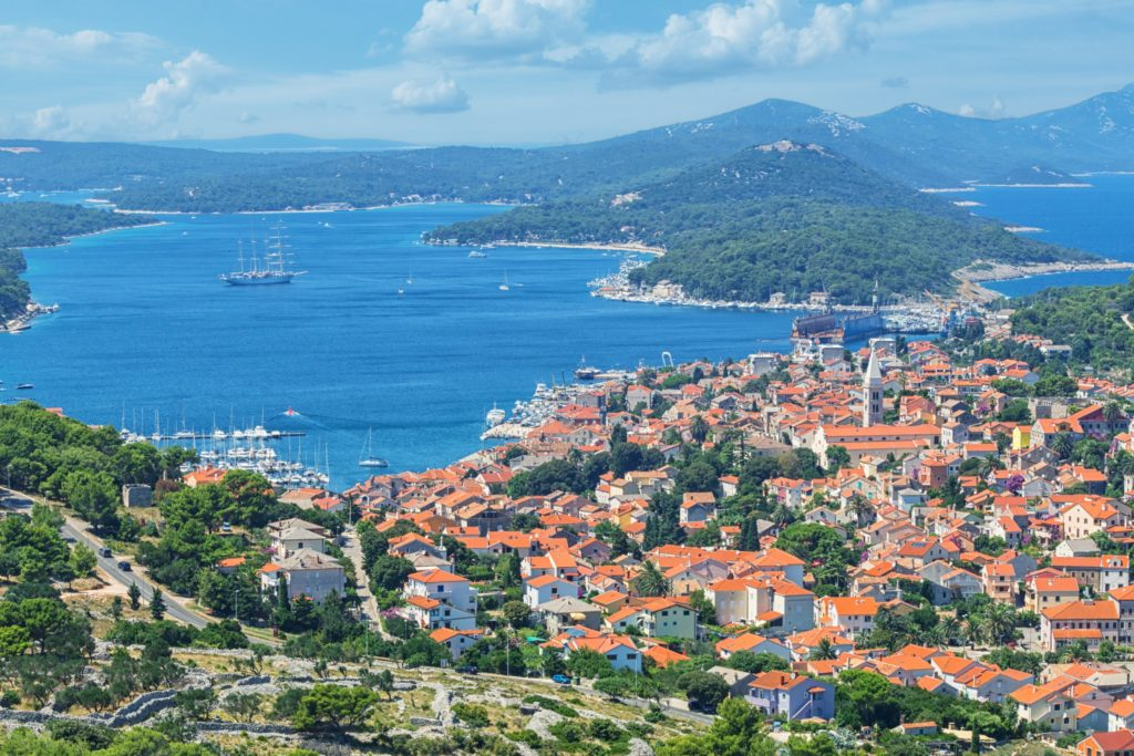 An aerial view of Mali Losinj presenting the buildings on land, the port and the surrounding islands