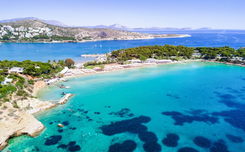 Aerial view of a bay in Athens with the surrounding greenery and clear blue seawater