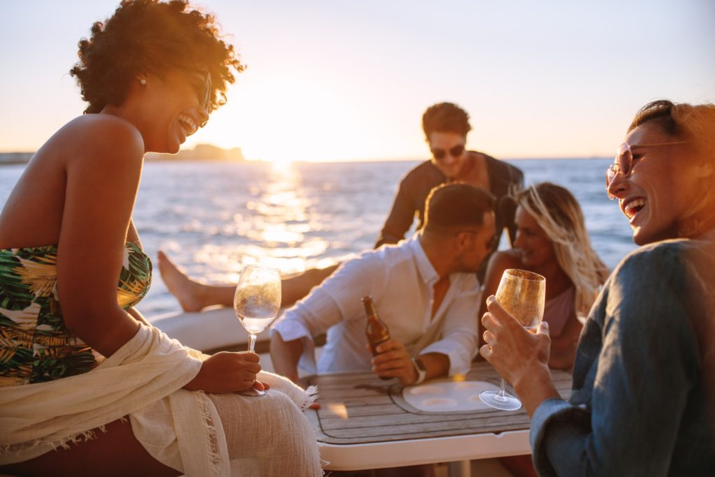 View of a group of friends on the boat in the sunset having fun and drinking