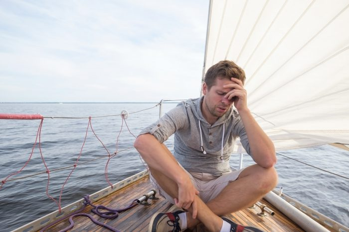 A view of a man feeling unwell on a sailing boat
