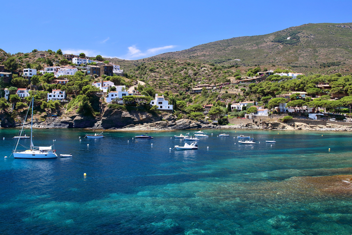 View of the bay in Sa Conca in the Costa Brava region showing some buildings in the hillside and boats anchoring