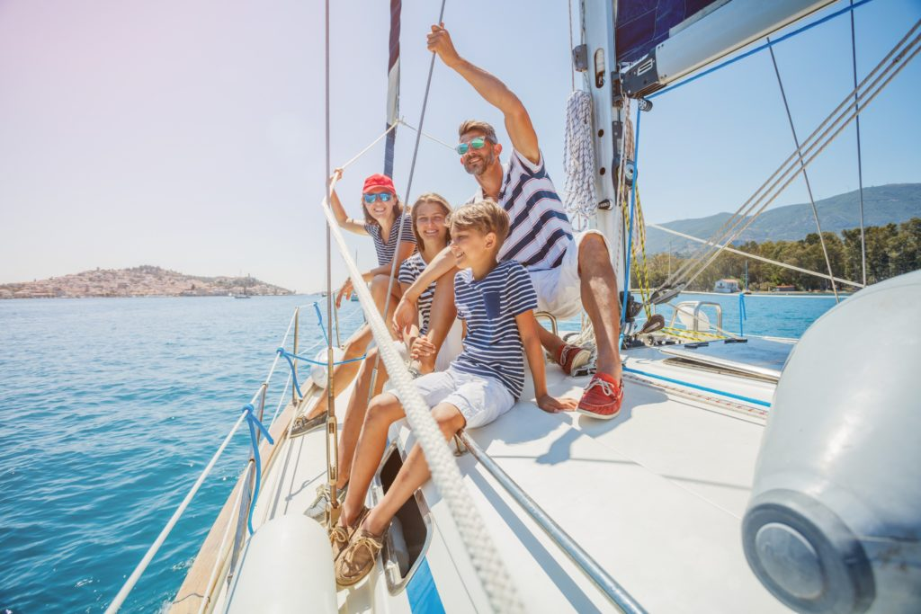 View of a happy family on a sailing boat in the middle of the sea
