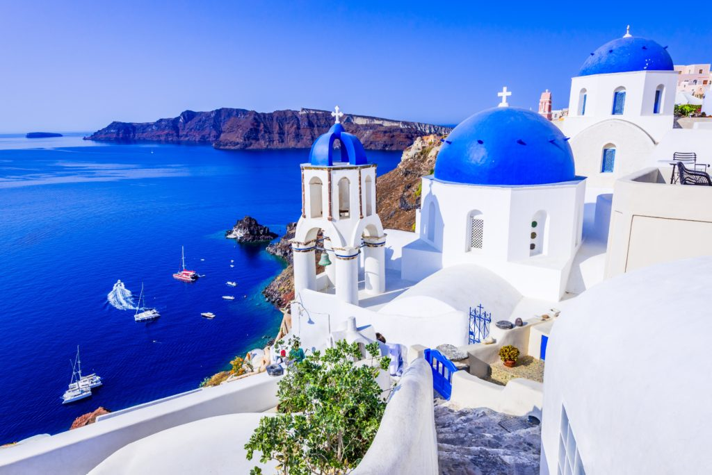 Aerial view of the whitewashed buildings on the side of the cliffs in Greece and the blue water