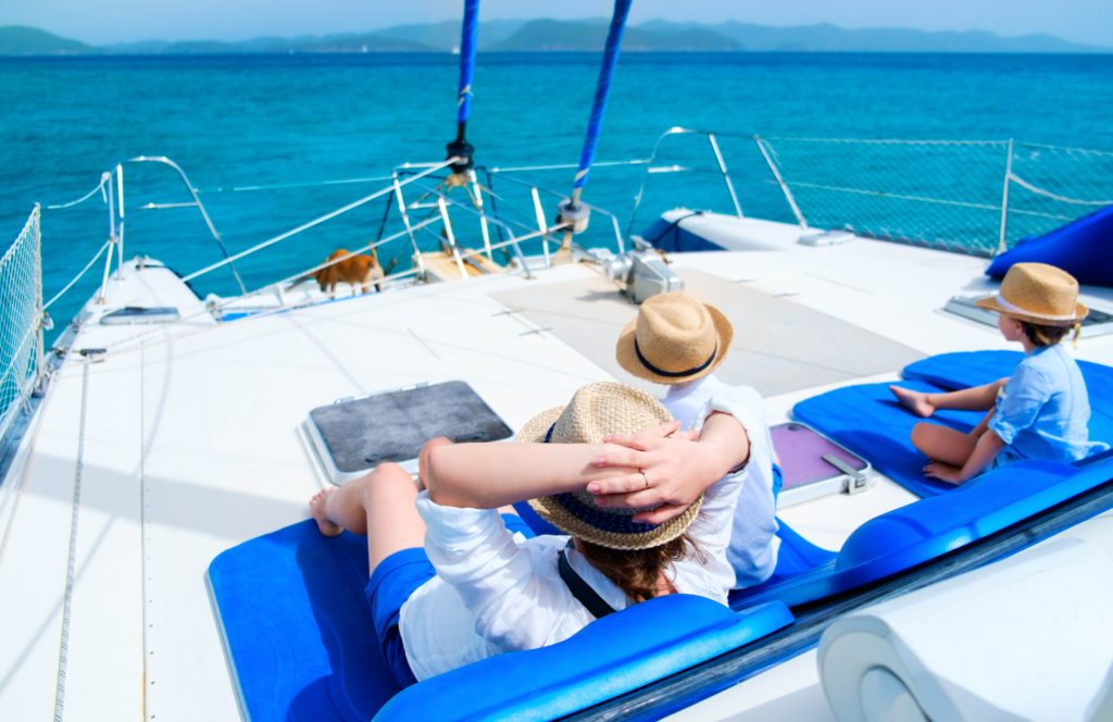 View of a family of 3 on a catamaran in the middle of the sea