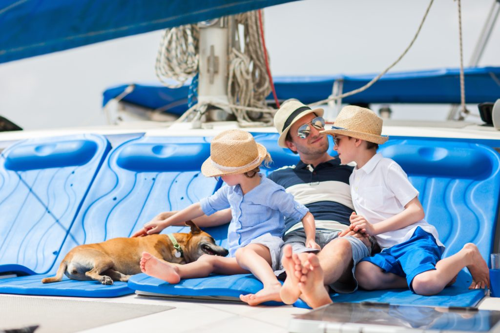 A father and two kids on the deck of a sailboat with their dog
