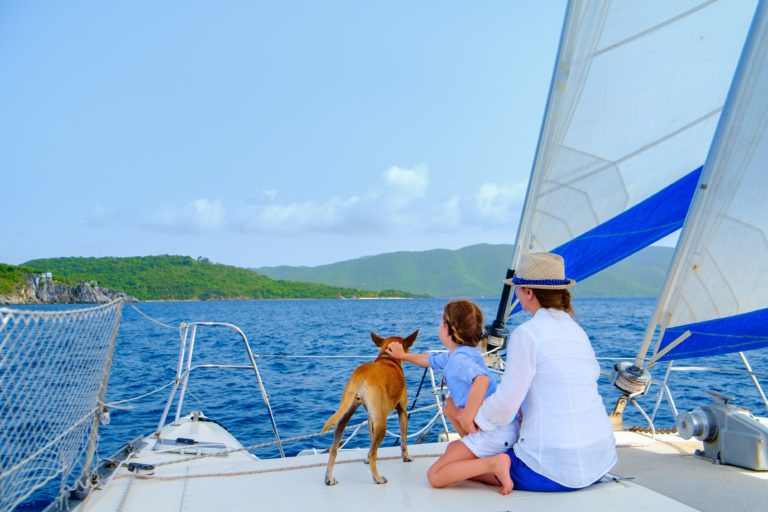 Mother and daughter on a sailboat with their dog on board