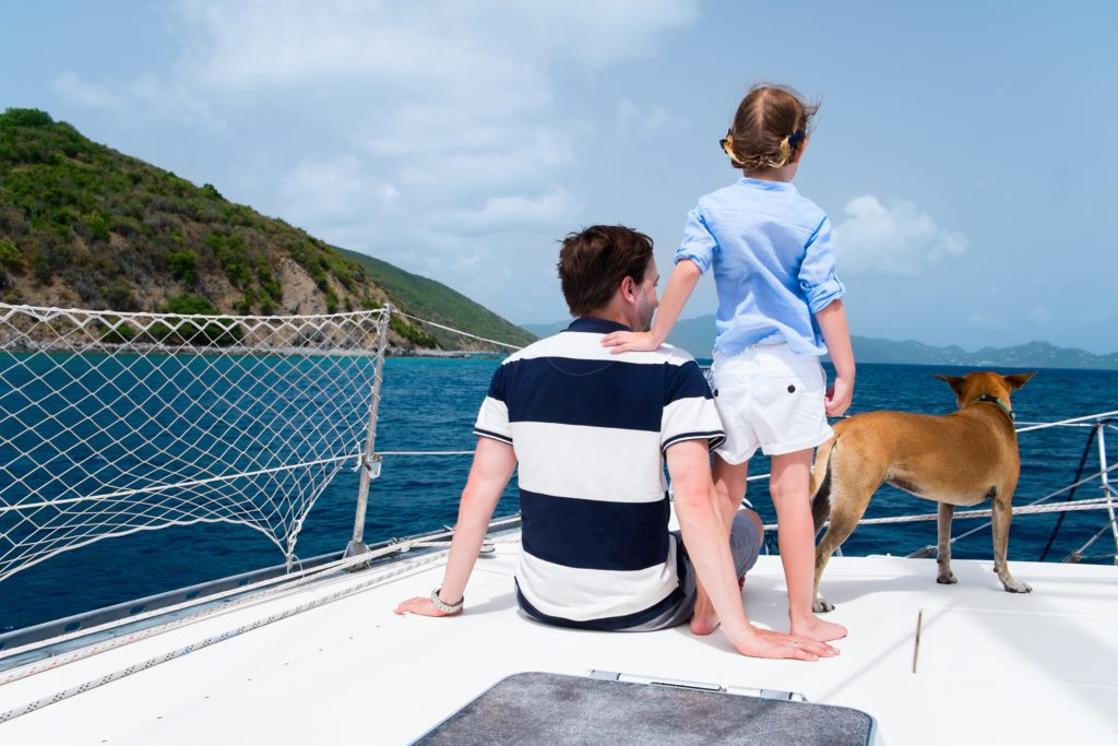 Father and daugther is sailing with a dog on a sailboat
