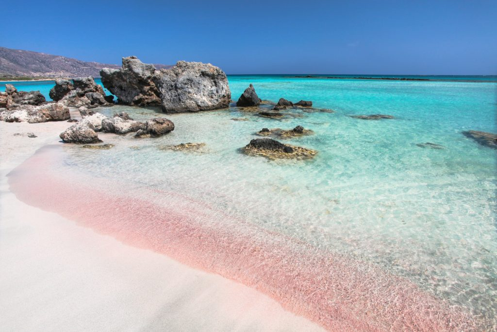 View of the Elafonisi Beach in Create showing the pink sand and some rocks in the clear sea