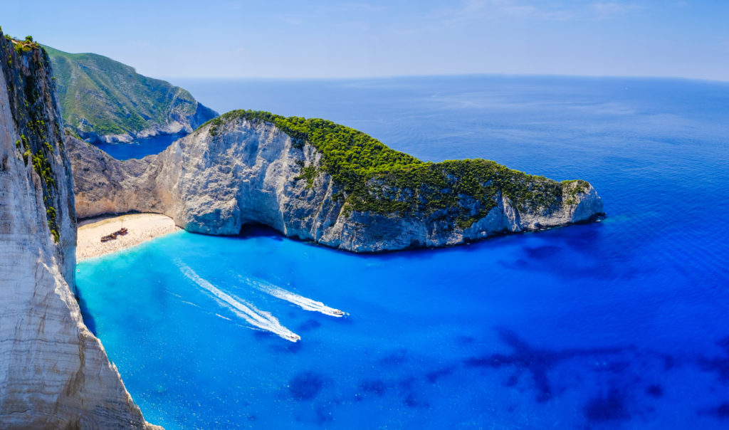 Aerial view of the Navagio Beach in Zakynthos, showing the sharp cliffs and clear blue water