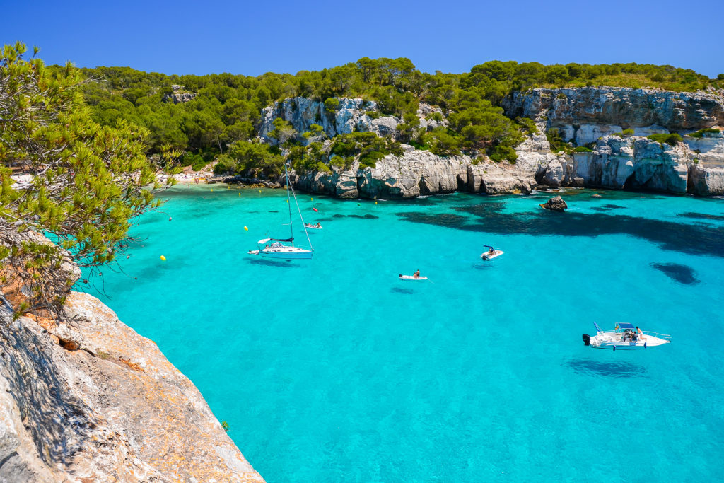 View of the Cala Macarella Beach in Menorca with the surrounding cliffs, a few boats and crystal clear water