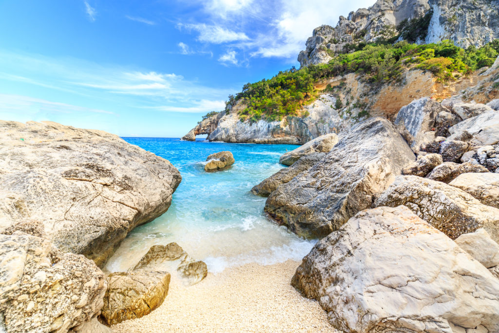 View of the Cala Goloritze beach in Sardinia showing the rocks on the sandy beach and the clear water