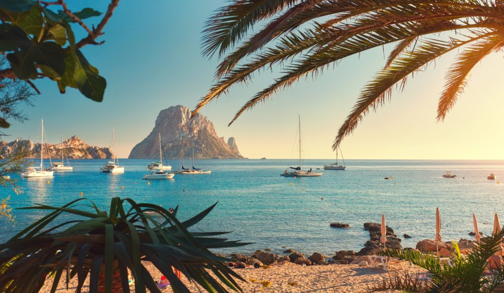 View of a sandy bay in Ibiza with boats and the landscape in the background