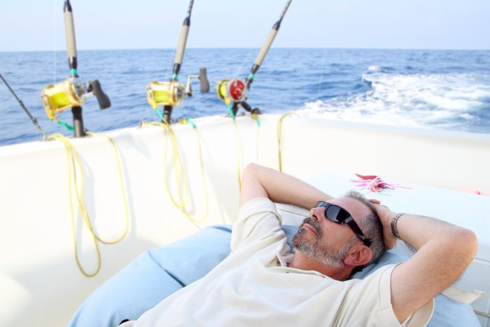 A man lying down on the deck of the boat