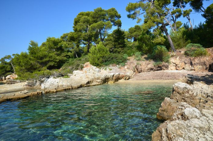 View of a stunning bay in France showing clear blue sea with surrounding cliffs and trees