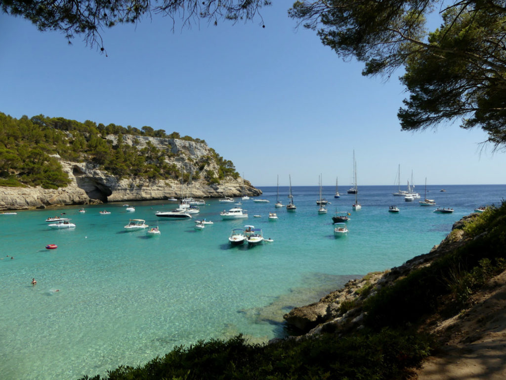 View of the Trebaluger Cove in Menorca showing some anchoring boats and the surrounding cliffs