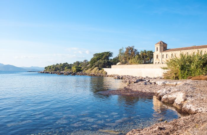 View of a beautiful beach on the island of Saint Honorat showing the rocks and buildinds along the beach