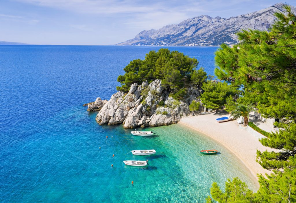 View of a coast in Croatia with 3 boats anchoring, clear blue sea, sandy beach and surrounding greenery