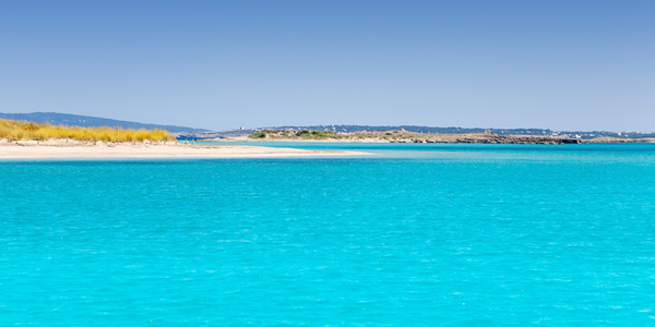 View of a beach in Espalmador showing the bright blue sea and white sandy beach