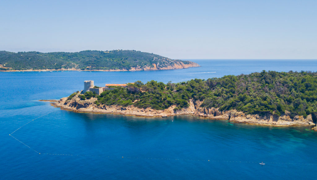 Aerial view of the Port Cros island showing the blue sea and stunning greenery on the island