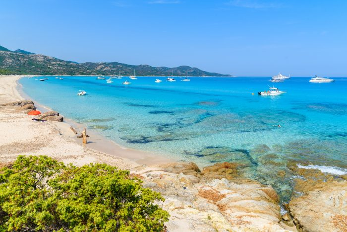 View of the Beach of Saleccia in Corsica showing crystal clear water, anchoring boats and sandy beach and rocks