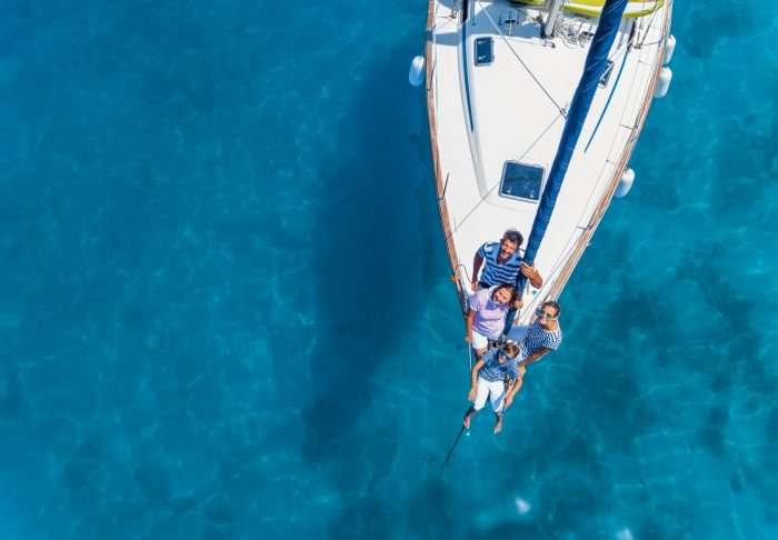 Aerial view of a family on a sailing boat in the middle of the sea
