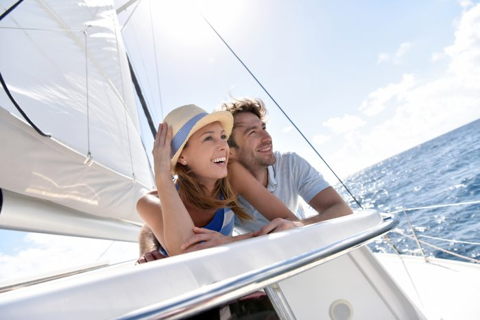 View of a happy couple laying on a sailing boat in the middle of the sea