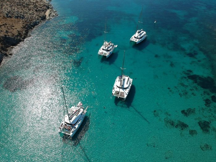 Aerial view of 4 catamarans in the middle of the clear blue sea
